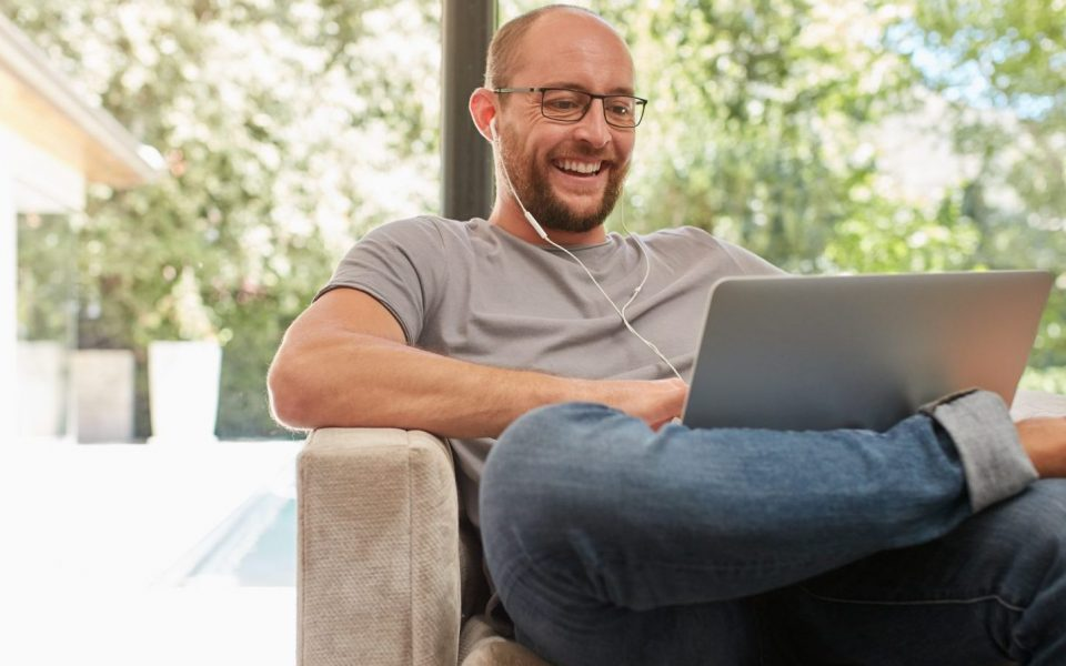 Indoor shot of a happy mature man having video call with laptop and earphones while sitting on the couch at home. Caucasian man using laptop and smiling.