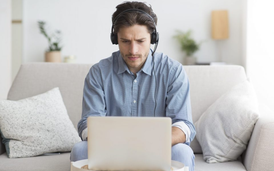 Online Education. Serious Student Guy In Headphones Studying At Laptop Sitting On Couch At Home. Selective Focus